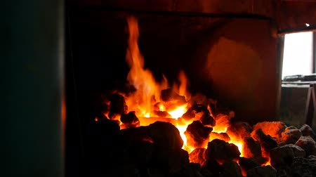 金属細工 : An incandescent furnace in the smithy with coals in which lie red-hot metal parts, heat treatment of details, forge, slow motion