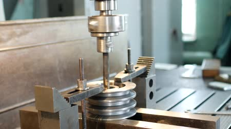 repairer : Drilling a hole with a drilling machine in a metal workpiece pulley, close-up, industry