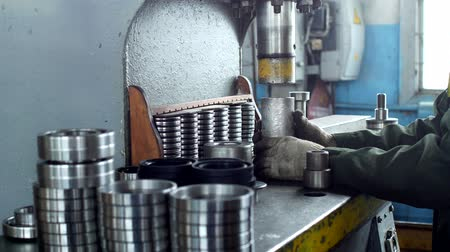franzir : The worker assembles the pressing of the bearing into a metal clip on the machine, assembles the finished unit, close-up, press, working