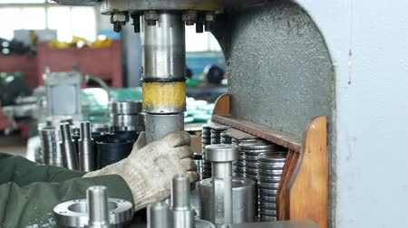 franzir : The worker at the plant presses the bearing into the hub using a press machine, assembling the hub, assembling the unit for mechanical engineering, close-up, adjustment