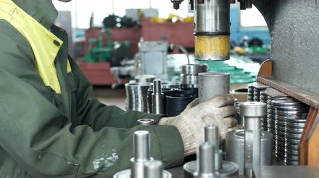 ayarlama : The worker at the plant presses the bearing into the hub using a press machine, assembling the hub, assembling the unit for mechanical engineering, close-up