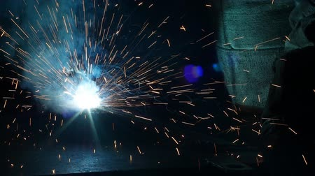 spawacz : Welding of metal parts, a lot of sparks and smoke, close-up, industry, slo-mo,