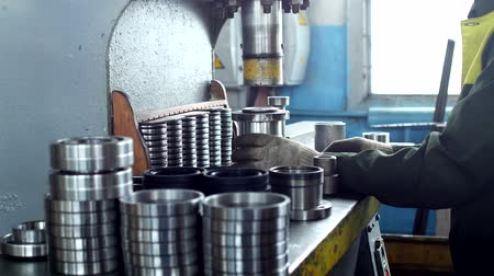 ayarlama : The worker assembles the pressing of the bearing into a metal clip on the machine, assembles the finished unit, close-up, press, hand