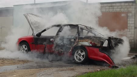vandalismo : firefighters or firemen extinguish a burnt car, automobile was not insured
