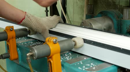 workman : Production and manufacturing of pvc windows, a female worker installs a pvc profile in the machine and drills a hole under the handle, close-up, drill