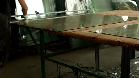 pvc frames : Workshop for the production of insulating glass, the worker cuts glass with glass cutter for further assembly of the insulating glass unit, glass cutting