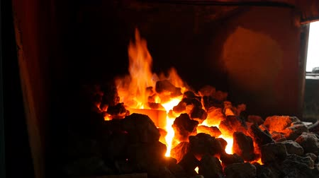 ручная работа : An incandescent furnace in the smithy with coals in which lie red-hot metal parts, heat treatment of details, forge, smith, slow-mo
