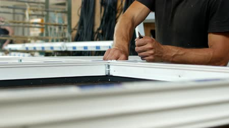 double glazed windows : Manufacturing and manufacturing of PVC windows, a male worker installs a rubber seal in a PVC frame, assembles a PVC window, compressor Stock Footage