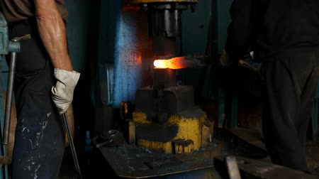 smithy : The smith in the forge forges a metal hot piece with the help of a jackhammer, pieces of scale, slow motion