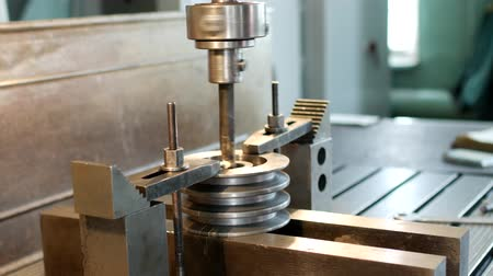 kütük : Drilling a hole with a drilling machine in a metal workpiece pulley, close-up, industry, block