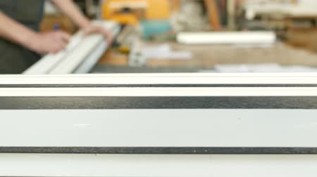 pvc frames : Production and manufacturing of pvc windows, the worker marks the size with a plastic pvc profile marker
