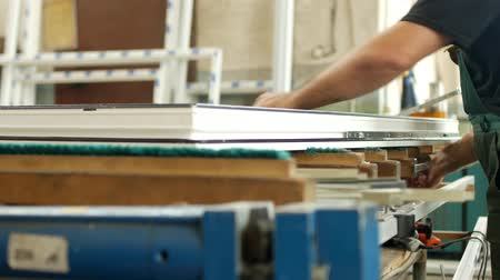 double glazed windows : Manufacturing and manufacturing of PVC windows, a man working on a pvc profile window, hangs up a snap, assembly window Stock Footage