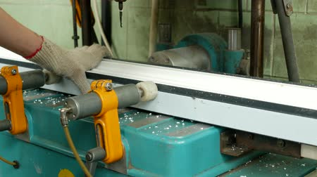 packet : Production and manufacturing of pvc windows, a female worker installs a pvc profile in the machine and drills a hole under the handle, close-up, drill pvc profile
