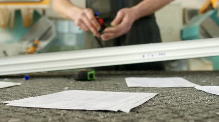 pvc frames : Production and manufacturing of pvc windows, a male worker is measuring a pvc profile piece and marking with a marker, tape-line Stock Footage