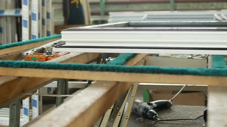 pvc frame : Production and manufacturing of plastic windows pvc, on the table lies the sash window, screwdriver, the shop is finished products windows Stock Footage