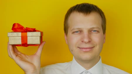 into the camera : man with gift inside the box smiles and looks into the camera, on yellow wall background Stock Footage
