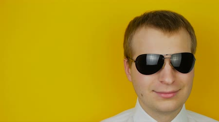 fröhlich : Portrait of smiling man in white shirt with black glasses, on yellow wall background