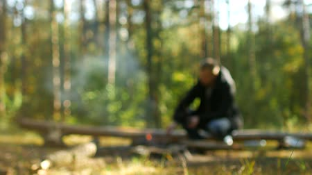 wood glade : A man kindles a fire in the woods in nature, outdoor recreation, blurry, background, camping Stock Footage