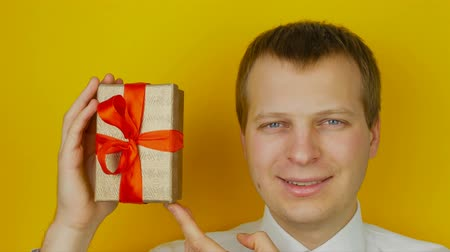 into the camera : guy with surprise inside the box smiles and looks into the camera, on yellow wall background