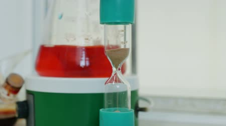 analyzes : hourglass and flask with liquid in medical laboratory