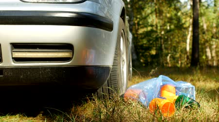 packet : A blue bag with plastic bottles of rubbish lies on the nature near the car, pollution of the nature by plastic waste, garbage and a car, litter