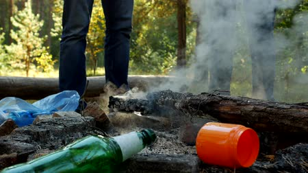 discard : Camping, a person extinguishes a fire with water and leaves leaving behind a clearing with garbage, garbage and nature, pollution Stock Footage