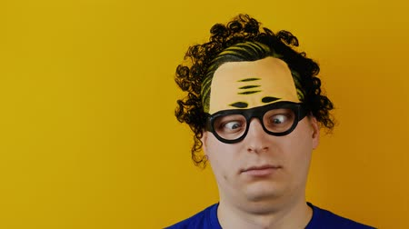 botanikus : insane curly guy with strabismus turns or rolls his eyes, black hairs, crazy and cheerfully human emotion, on yellow wall background