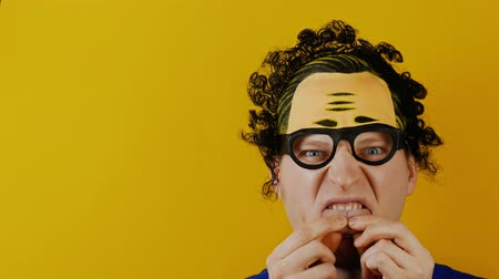 botanikus : insane man holds his tongue by his fingers, curly black hairs, funny cheerfully human emotions, on yellow wall background Stock mozgókép