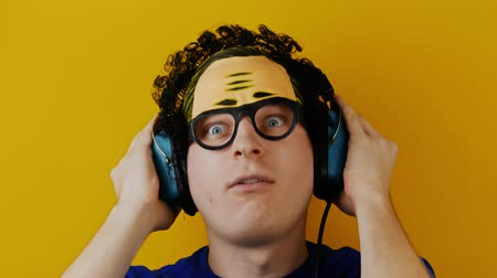 çuval : crazy comical curly guy listening to music in a retro headphones or earphones Stok Video