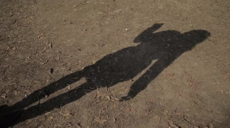 terénní : The shadow on the ground of a girl walking along the road, slow-mo, girls shadow