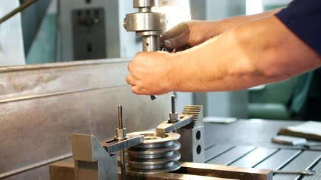 repairer : The man specialist checks the measuring tool with the size of drilling a metal pulley and inserts a drill into a drilling machine, individual entrepreneur
