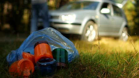 packet : A package of garbage with plastic bottles is lying on the nature, in the background there is a car and people are walking, nature pollution with plastic waste, a car in nature and garbage, rubbish