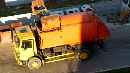 szemét : A garbage truck cleans garbage cans in the courtyard of a residential area from garbage and takes it to landfill Stock mozgókép