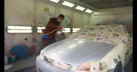 repaint : Footage of a car being painted and varnished in a painting chamber