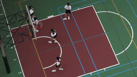 equipamentos esportivos : School kids playing basketball at a basketball court