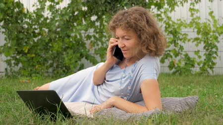 легкий : Woman talking by phone and working with notebook.