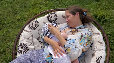 loved : Caucasian woman with newborn baby girl in the garden. Stock Footage