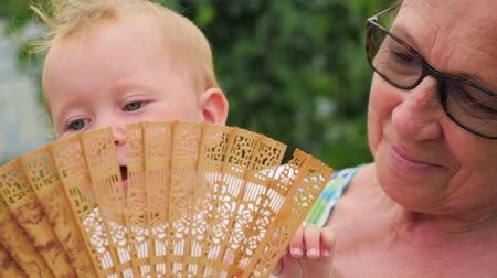 чувствовать : Woman and child. Older and younger. Beautiful ladies. Toddler playing with fan on grandmothers hands.