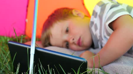 looking for : Child with tablet lying on green grass under sun umbrella. Summer vacation concept. Stock Footage