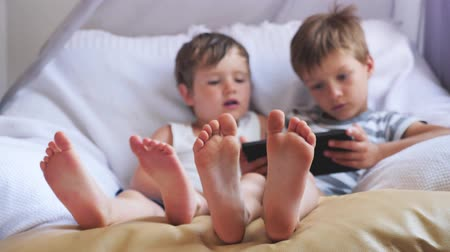 ayak parmakları : Two cute boys taking a rest at daytime. Focus on boys feet.