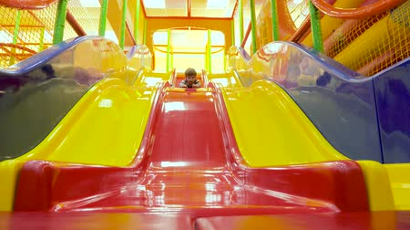 renovar : Child sliding down colorful slide play house in backyard. Sports and recreations for children. Plays and games for kids. Modern lifestyle background. Childs Excitement while sliding down.