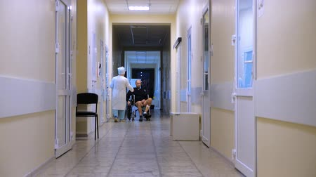 kayış : Male with leg burns on a wheelchair at hospital. View of a hospital hall. People in a clinic hall, walking. Medical facility. Hospital, clinic, private clinic. Medical reform. Pharmaceutical industry
