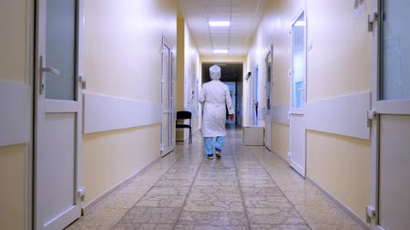 walking back : Adult male doctor is passing by the hospital hall. View of a hospital hall. Empty clinic corridor with doctor. Private clinic, medical center. Medical reform of traditional non-traditional medicine. Stock Footage