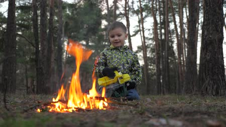 treating : Boy staring at fireplace. Arson background. Beautiful kid warming up at the fire. When war comes to native home. Refugee background. Exploring the world.
