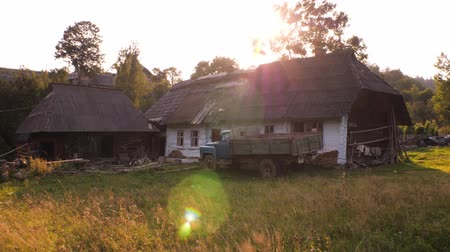 settlement : Old rural houses, beautiful courtyard. Carpathian Ukraine. Village household with stable and car on front yard. Natural economy. Eco style of living.
