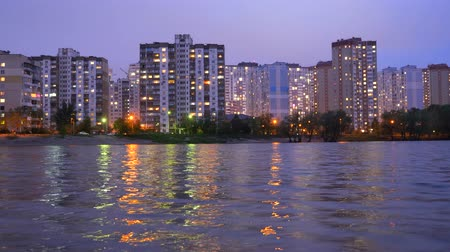 předměstí : A complex of appartment buildings in the evening city near the large lake, with street lights reflecting in the water. Buildings in twilight near lake. Buildings and lights in appartments evening. Dostupné videozáznamy
