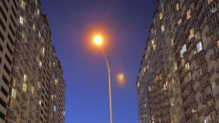 předměstí : Nighttime time lapse of illuminated building windows at night with people living in flats with balcony. Electricity consumption concept. View from below. City street in evening