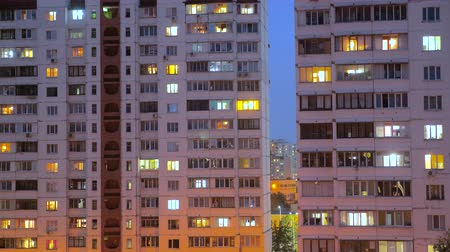consumo : Nighttime time lapse of illuminated building windows at night with people living in flats with balcony. Electricity consumption concept. View from below. City street in evening