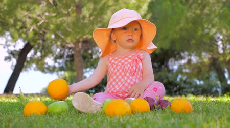 апельсины : Child sitting on green grass. Child in panama having fun outdoor on back yard. Happy childhood concept. Toddler sitting on green grass waiting for mother. Little princess playing with fruits outdoor. Стоковые видеозаписи