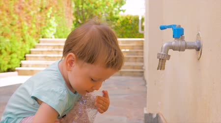 reutilizável : Little baby girl playing with water. Toddler playing with water flowing from tap. Kid holding empty plastic bottle near tap. Water problems background. Fresh water problems. Kindergarten concept